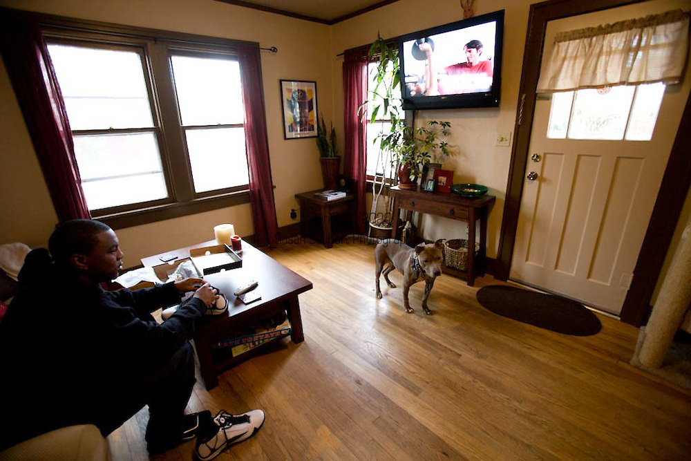 Steven, friend of Margaret B. Jones, watching tv in her living room. He is staying with her while recuperating from a gunshot wound to the leg.  Her pit bull, Flue, is standing near the door.