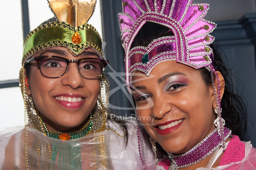 London, August 25th 2014. Two women wait for a break in the rain as final touch ups to costumes are made as Notting Hill Carnival goers prepare to party despite the pouring rain.