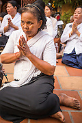 """03 FEBRUARY 2013 - PHNOM PENH, CAMBODIA: A woman prays on the street during the final Buddhist chanting service for former Cambodian King Norodom Sihanouk in the crematorium built for the King's funeral at the National Museum in Phnom Penh. Norodom Sihanouk (31 October 1922- 15 October 2012) was the King of Cambodia from 1941 to 1955 and again from 1993 to 2004. He was the effective ruler of Cambodia from 1953 to 1970. After his second abdication in 2004, he was given the honorific of """"The King-Father of Cambodia."""" He served as puppet head of state for the Khmer Rouge government in 1975-1976, before going into exile. Sihanouk's actual period of effective rule over Cambodia was from 9 November 1953, when Cambodia gained its independence from France, until 18 March 1970, when General Lon Nol and the National Assembly deposed him. Upon his final abdication in 2004, the Cambodian throne council appointed Norodom Sihamoni, one of Sihanouk's sons, as the new king. Sihanouk died in Beijing, China, where he was receiving medical care, on Oct. 15, 2012. His cremation will take place on Feb. 4, 2013. Over a million people are expected to attend the service.     PHOTO BY JACK KURTZ"""