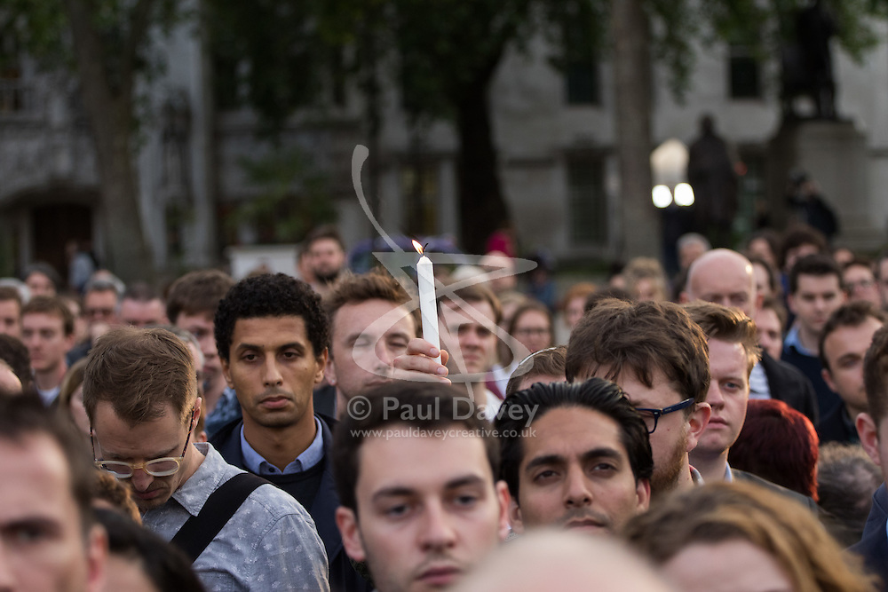 Parliament Square, Westminster, London, June 17th 2016. Following the murder of Jo Cox MP a vigil is held as friends and members of the public lay flowers, light candles and leave notes of condolence and love in Parliament Square, opposite the House of Commons. PICTURED: A candle is held aloft during the two-minute silence.