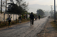 Burma/Myanmar, Nyaungshwe. People and bicycles on the road in Nyaungshwe early in the morning.