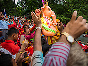 31 AUGUST 2014 - SARIKA, NAKHON NAYOK, THAILAND: A statue of Ganesh is carried to the river to be submerged during the Ganesh Festival at Shri Utthayan Ganesha Temple in Sarika, Nakhon Nayok. Ganesh Chaturthi, also known as Vinayaka Chaturthi, is a Hindu festival dedicated to Lord Ganesh. It is a 10-day festival marking the birthday of Ganesh, who is widely worshiped for his auspicious beginnings. Ganesh is the patron of arts and sciences, the deity of intellect and wisdom -- identified by his elephant head. The holiday is celebrated for 10 days, in 2014, most Hindu temples will submerge their Ganesh shrines and deities on September 7. Wat Utthaya Ganesh in Nakhon Nayok province, is a Buddhist temple that venerates Ganesh, who is popular with Thai Buddhists. The temple draws both Buddhists and Hindus and celebrates the Ganesh holiday a week ahead of most other places.    PHOTO BY JACK KURTZ
