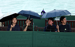 Spectators shelter under umbrellas during a rain delay on day three of the Wimbledon Championships at the All England Lawn Tennis and Croquet Club, Wimbledon.
