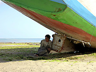 A local man rests beneath a boat on a beach in Tanah Beru, South Sulawesi, Indonesia, Southeast Asia