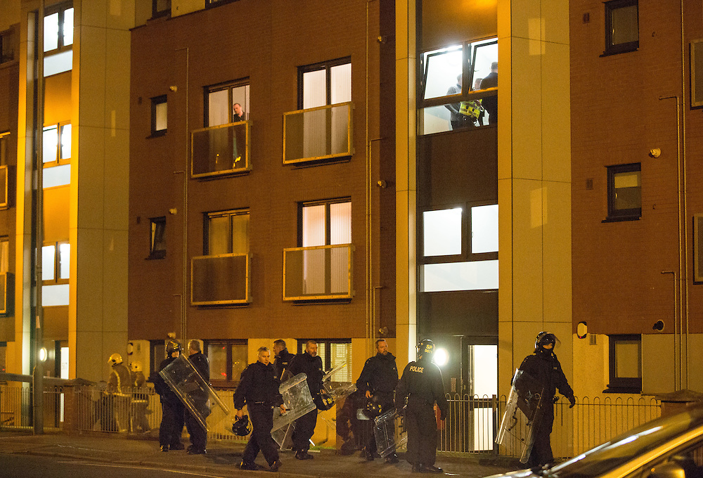 Police attend a siege situation in Old Shettleston Road, Glasgow. The suspect's next door neighbour looks from his window as police leave the flat.  Picture Robert Perry 14th April 2016<br /> <br /> Must credit photo to Robert Perry<br /> FEE PAYABLE FOR REPRO USE<br /> FEE PAYABLE FOR ALL INTERNET USE<br /> www.robertperry.co.uk<br /> NB -This image is not to be distributed without the prior consent of the copyright holder.<br /> in using this image you agree to abide by terms and conditions as stated in this caption.<br /> All monies payable to Robert Perry<br /> <br /> (PLEASE DO NOT REMOVE THIS CAPTION)<br /> This image is intended for Editorial use (e.g. news). Any commercial or promotional use requires additional clearance. <br /> Copyright 2014 All rights protected.<br /> first use only<br /> contact details<br /> Robert Perry     <br /> 07702 631 477<br /> robertperryphotos@gmail.com<br /> no internet usage without prior consent.         <br /> Robert Perry reserves the right to pursue unauthorised use of this image . If you violate my intellectual property you may be liable for  damages, loss of income, and profits you derive from the use of this image.