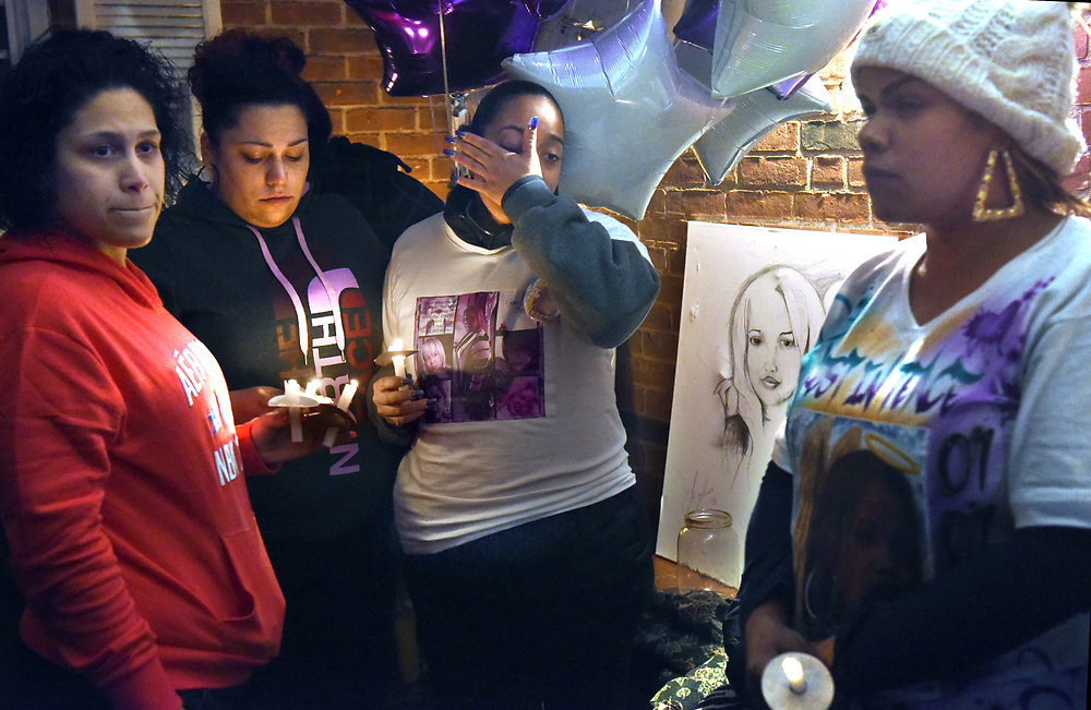 Hartford, CT, 01/04/2017<br /> A candlelight vigil was held in memory of Luz Rosado, outside her Hartford family's home. Rosado was the first homicide in Hartford in 2017. From left: friends of Rosado's Lissette Ortega and her sister Venessa (cq) Ortega both of Manchester; Rosado's sister Yaritza Rosado of Hartford; Rosado's friend Chastity Casiano of Hartford. The drawing is of Luz Rosado.<br /> Photo by MARA LAVITT | Special to the Courant.