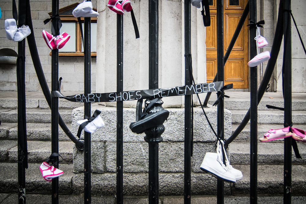 """Dublin, Ireland. 26th August, 2018. <br /> As symbol of the protest has been chosen babyshoes, here on the gate of St. Mary Pro Cathedral, in Marlborough Street just ahead the Mass during the second of the two-days of the visit of Pope Francis in Dublin, Ireland.<br /> Pope Francis has made a two-day visit to the Republic of Ireland by celebrating a Mass at Dublin's Phoenix Park. The Argentine Pope asked forgiveness for the """"abuses in Ireland, abuses of power, conscience and sexual abuses"""" perpetrated by Church leaders. It was the first papal visit to Ireland for 39 years. During his activities many activists, victims and survivors have made protests and a silent march Garden of Remembrance towards the last Magdalene Laundry to close in Ireland.<br />  © Simone Padovani"""