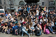 Summertime in London, England, UK. Student tourists gather en masse at the base of Eros in Piccadily Circus.