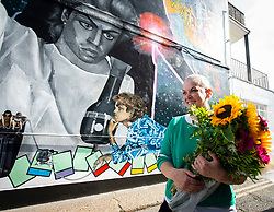 A 9 metre George Michael mural painted in Kingsbury by artist Dawn Mellor, North West London, Great Britain <br />Unveiled 17th September 2020    <br /><br />Dawn Mellor holds flowers presented by fans by her mural <br /><br />A large-scale mural that celebrates the life of local hero George Michael who was a 1st year pupil at Kingsbury High School in 1974. <br />Commissioned as part of the Brent supported by the Brent Borough of Culture 2020 fund. <br /><br />Photograph by Elliott Franks