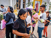29 DECEMBER 2013 - BANGKOK, THAILAND:  People light candles and incense in honor of the Thai Patriarch (whose photo is in the background)  at Wat Bowon Niwet in Bangkok. Somdet Phra Nyanasamvara, who headed Thailand's order of Buddhist monks for more than two decades and was known as the Supreme Patriarch, died Oct. 24 at a hospital in Bangkok. He was 100. He was ordained as a Buddhist monk in 1933 and rose through the monastic ranks to become the Supreme Patriarch in 1989. He was the spiritual advisor to Bhumibol Adulyadej, the King of Thailand when the King served as monk in 1956. There is a 100 day mourning period for the Patriarch. Although the Patriarch was a Theravada Buddhist, he was the Supreme Patriarch of all Buddhists in Thailand, including the Mahayana sect, which is based on Chinese Buddhism.       PHOTO BY JACK KURTZ