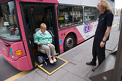 Bus driver ensuring woman wheelchair user descends ramp from the bus safely,