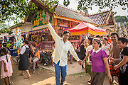 16 MARCH 2013 - ALONG HIGHWAY 13, LAOS:  A man dances while people walk around him at the temple fair at Wat Nong Sa in the village of Nong Sa, which is on Highway 13, in Vientiane province of Laos. The paving of Highway 13 from Vientiane to near the Chinese border has changed the way of life in rural Laos. Villagers near Luang Prabang used to have to take unreliable boats that took three hours round trip to get from the homes to the tourist center of Luang Prabang, now they take a 40 minute round trip bus ride. North of Luang Prabang, paving the highway has been an opportunity for China to use Laos as a transshipping point. Chinese merchandise now goes through Laos to Thailand where it's put on Thai trains and taken to the deep water port east of Bangkok. The Chinese have also expanded their economic empire into Laos. Chinese hotels and businesses are common in northern Laos and in some cities, like Oudomxay, are now up to 40% percent. As the roads are paved, more people move away from their traditional homes in the mountains of Laos and crowd the side of the road living off tourists' and truck drivers.   PHOTO BY JACK KURTZ