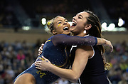 Olivia Karas of the Michigan Wolverines hugs assistant coach Maile'Ana Kanewa-Hermelyn after competing on beam at the NCAA Regional at Crisler Center on April 6, 2019 in Ann Arbor, Michigan.