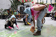 Extinction Rebellion 'Dirty Scrubbers' old fashioned washer women in curlers clean up the soap from their bubble machines after laundering their 'dirty money' and greenwash stains in the City of London financial district in a performance designed to highlight the corruption of big business and banking on 9th September 2020 in London, United Kingdom. Here the protest is outside <br /> BlackRock: Investment Management & Financial Services. The activists shouted out for people to come from the banks and to bring their dirty money to be cleaned in their washing machines. Extinction Rebellion is a climate change group started in 2018 and has gained a huge following of people committed to peaceful protests. These protests are highlighting that the government is not doing enough to avoid catastrophic climate change and to demand the government take radical action to save the planet.
