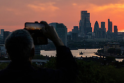 © Licensed to London News Pictures. 01/06/2021. London, UK. People in Greenwich Park watch the sun setting over the London skyline on the first day of meteorological summer, as warm weather continues across much of the United Kingdom. Photo credit: Rob Pinney/LNP