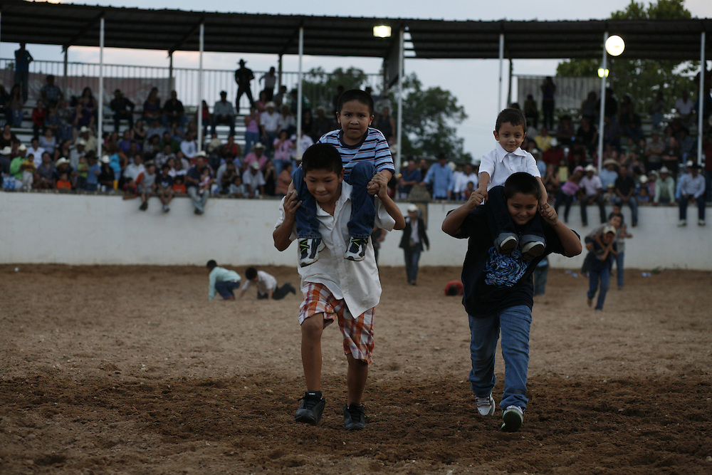 Children race through the lienzo during a break from the action at El Bajio in Von Ormy, Texas.  The charreada is a family event and lienzos in central Texas strive to make it entertaining for everyone.  Mariachis and ballet folklorico troupes are common additions to the suertes.