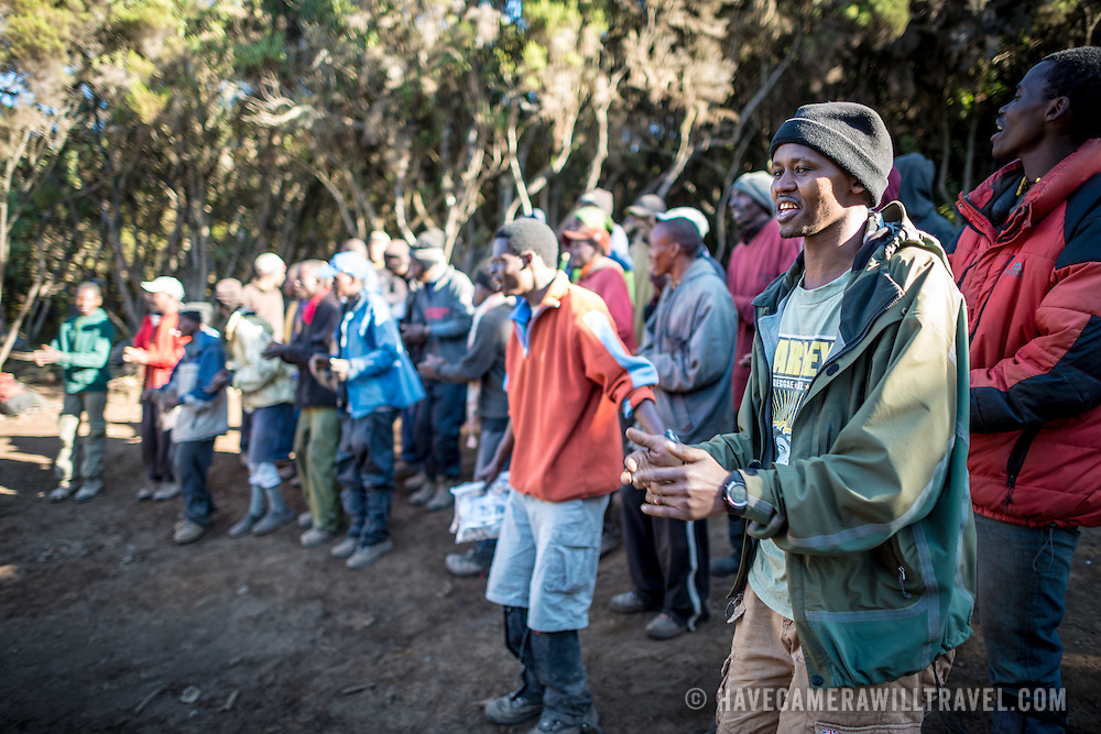 """Porters perform a song and dance as a farewell to their group of hikers at Mweka Camp on Mt Kilimanjaro. The """"Kilimanjaro Song"""" is a standard."""