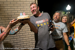 "Robert ""Big Swede"" Gustavsson gets a birthday cake at his parking lot Pizza Party from host Dean ""Dino"" Bordigioni after stage 12 (299 m) of the Motorcycle Cannonball Cross-Country Endurance Run, which on this day ran from Springville, UT to Elko, NV, USA. Wednesday, September 17, 2014.  Photography ©2014 Michael Lichter."