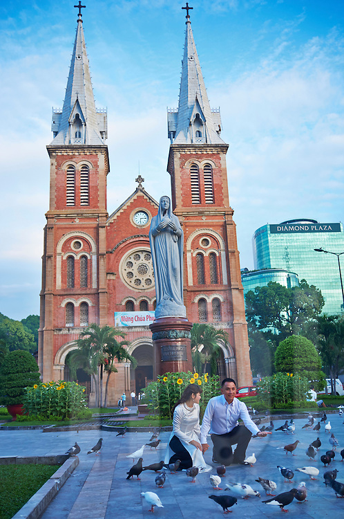 A Vietnamese couple poses in front of Notre Dame Basilica for a photograph, Ho Chi Minh city, Vietnam, Southeast Asia