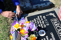 Debra Parcasio cleans the grave of her father and mother-in-law at Garden of Memories Memorial Park on Monday in Salinas. Ben Parcasio, a veteran and survivor of the Bataan Death March, died in 1997 - his wife, Cipriana Quirante, in 2009.
