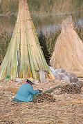 Uru woman making repairs to Reed house, Lake Titicaka, Puno, Peru, South America