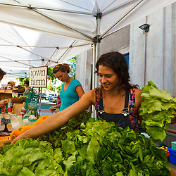 Mia Valentini (right) and Morgan Brown (center), work the Town Farm booth at the Tuesday Market farmer's market in Northampton, Massachusetts.