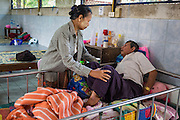 05 MARCH 2014 - MAE SOT, TAK, THAILAND: A woman massages her husband's leg in the general ward at the Mae Tao Clinic. The man came to the clinic with leg pain. The Mae Tao Clinic provides  healthcare to over 150,000 displaced Burmese per year and is the leading healthcare provider for Burmese along the Thai-Myanmar border. Reforms in Myanmar have alllowed NGOs to operate in Myanmar, as a result many NGOs are shifting resources to operations to Myanmar, leaving Burmese migrants and refugees in Thailand vulnerable.     PHOTO BY JACK KURTZ