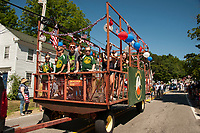 Children wave to the crowd from the Gilmanton Youth Organization float during Gilmanton's 4th of July parade on Wednesday morning.  (Karen Bobotas/for the Laconia Daily Sun)