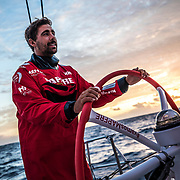 Leg 4, Melbourne to Hong Kong, day 18 on board MAPFRE, Guillermo Altadill stearing suring the sun rise. Photo by Ugo Fonolla/Volvo Ocean Race. 18 January, 2018.