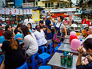 """18 MAY 2017 - BANGKOK, THAILAND: A worker seats customers at a street food stall in Bangkok's Chinatown. City officials in Bangkok have taken steps to rein in street food vendors. The steps were originally reported as a """"ban"""" on street food, but after an uproar in local and international news outlets, city officials said street food vendors wouldn't be banned but would be regulated, undergo health inspections and be restricted to certain hours on major streets. On Yaowarat Road, in the heart of Bangkok's touristy Chinatown, the city has closed some traffic lanes to facilitate the vendors. But in other parts of the city, the vendors have been moved off of major streets and sidewalks.      PHOTO BY JACK KURTZ"""
