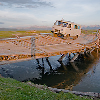 MONGOLIA.   Four-wheel drive van crosses dangerous bridge over river near Rinchenlhumbe in Darhad Valley.  This bridge washes out regularly in floods. Horidal Saridag Mountains bkg.