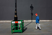 A tourist in red cap with a lamp post shadow against a grey construction hoarding in central London's Trafalgar Square. Painting work is being carried out to the street lighting lamp post, a green plastic fence surrounding the wet paint while the post's upright has created a strong linear theme to the pavement and background hoarding that screens other work.