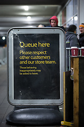 © Licensed to London News Pictures . 27/11/2015 . Salford , UK . A sign warning people to behave appropriately at the head of the queue for Black Friday reductions , at a branch of Tesco in Pendleton , Salford , this morning (Friday 27th November) . Last year (2014) scuffles and fights were reported amongst queuing bargain-hunters . Photo credit: Joel Goodman/LNP