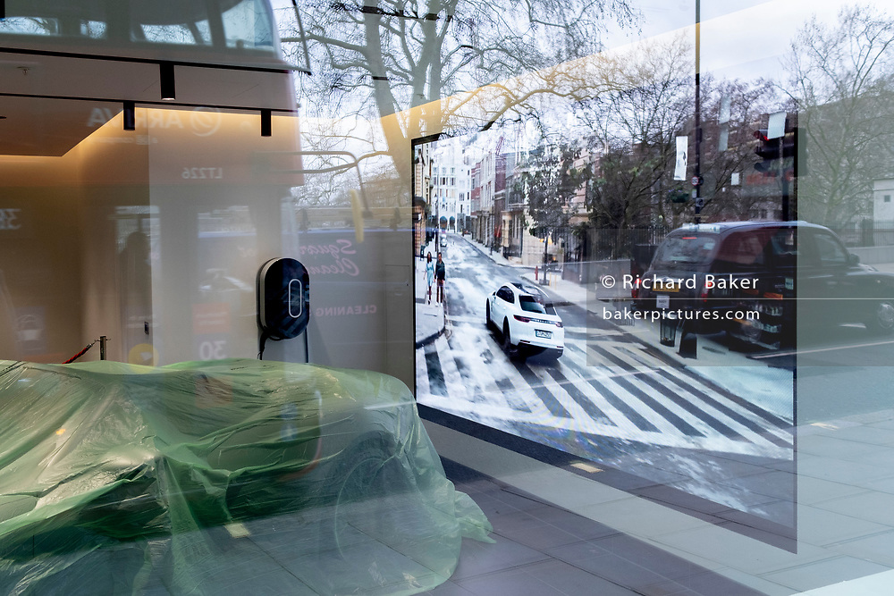 Protected against the dust during the closure of non-essential businesses during the Coronavirus pandemic, luxury Porsche cars are under cover in the company's Piccadilly showroom in London's West End, on 4th March 2021, in London, England.