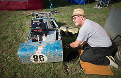 © Licensed to London News Pictures. 24/09/2016. Five Oaks, UK. A competitor prepares his mower ahead of a race at the Lawn Mower Racing World Championships. A weekend long set of races using specially adapted lawn mowers will see a World Champion announced on Sunday. Photo credit: Peter Macdiarmid/LNP