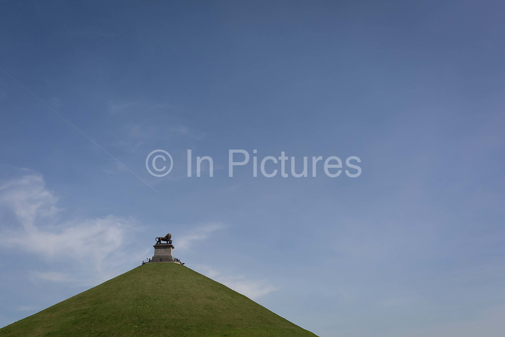Visitors on the top of  the 43 metre high Waterloo Lions battlefield Mound, on 25th March 2017, at Waterloo, Belgium. The Lions Mound Butte du Lion is a large conical artificial hill completed in 1826. It commemorates the location on the battlefield of Waterloo where a musket ball hit the shoulder of William II of the Netherlands the Prince of Orange and knocked him from his horse during the battle. From the summit, the hill offers a 360 degree vista of the battlefield. The Battle of Waterloo was fought 18 June 1815. A French army under Napoleon Bonaparte was defeated by two of the armies of the Seventh Coalition: an Anglo-led Allied army under the command of the Duke of Wellington, and a Prussian army under the command of Gebhard Leberecht von Blücher, resulting in 41,000 casualties.