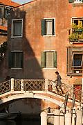 Woman crossing Rio de le Romite. Dorsoduro district. Venice, Italy, Europe