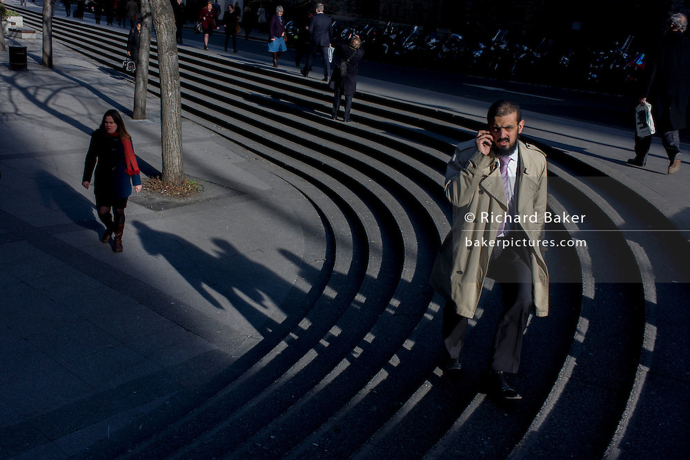 Businessmen on the lunch hour walk up steps in sunlight across a pedestrian precinct in the City of London.
