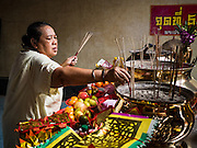 12 OCTOBER 2015 - BANGKOK, THAILAND:  A woman makes merit at Wat Mangkon Kamlawat, a large Chinese temple in Bangkok, on the first day of the Vegetarian Festival in Bangkok's Chinatown. The Vegetarian Festival is celebrated throughout Thailand. It is the Thai version of the The Nine Emperor Gods Festival, a nine-day Taoist celebration beginning on the eve of 9th lunar month of the Chinese calendar. During a period of nine days, those who are participating in the festival dress all in white and abstain from eating meat, poultry, seafood, and dairy products. Vendors and proprietors of restaurants indicate that vegetarian food is for sale by putting a yellow flag out with Thai characters for meatless written on it in red.     PHOTO BY JACK KURTZ