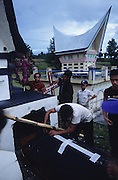 The actual burial ceremony during a Batak funeral..Batak Indigenous Christian people living on Samosir Island and nearby Lake Toba in Indonesia. There are some 6 million Christian Batak in Indonesia, the world's largest Muslim country of 237 million people, which has more Muslims than any other in the world. Though it has a long history of religious tolerance, a small extremist fringe of Muslims have been more vocal and violent towards Christians in recent years. ..Batak religion is found among the Batak societies around Lake Toba in north Sumatra. It is ethnically diverse, syncretic, liable to change, and linked with village organisations and the monotheistic Indonesian culture. Toba Batak houses are boat-shaped with intricately carved gables and upsweeping roof ridges, and Karo Batak houses rise up in tiers. Both are built on piles and are derived from an ancient Dong-Son model. The gable ends of traditional houses, Rumah Bolon or Jabu, are richly decorated with the cosmic serpent Naga Padoha carved in wood or in mosaic, lizards, double spirals, female breasts, and the head of the singa, a monster with protruding eyes that is part human, part water buffalo, and part crocodile or lizard. The layout of the village symbolises the Batak cosmos. They cultivate irrigated rice and vegetables. Irrigated rice cultivation can support a large population, and the Toba and the Karo live in densely clustered villages, which are limited to around ten homes to save farming land. The kinship system is based on marriage alliances linking lineages of patrilineal clans called marga. In the 1820's Islam came to the southern Angkola and Mandailing homelands, and in the 1850's and 1860's Christianity arrived in the Angkola and Toba region with Dutch missionaries and the German Rheinische Mission Gesellschaft. The first German missionary caused the Dutch to stop Batak communal sacrificial rituals and music, which was a major blow to the traditional religion. Dutch colonial policy favoure