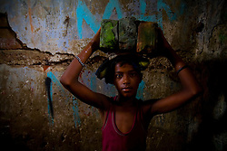 A child labor works at construction site in Dhaka, Bangladesh.