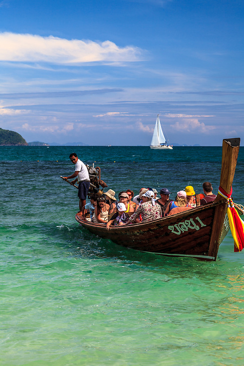 The long-tail boat or Ruea Hang Yao in Phuket, Thailand. People have used these wooden, banana-shaped boats in Thailand for hundreds of years. Today's versions are equipped with diesel engines connected to a thin, lengthy rudder that resembles a long tail.
