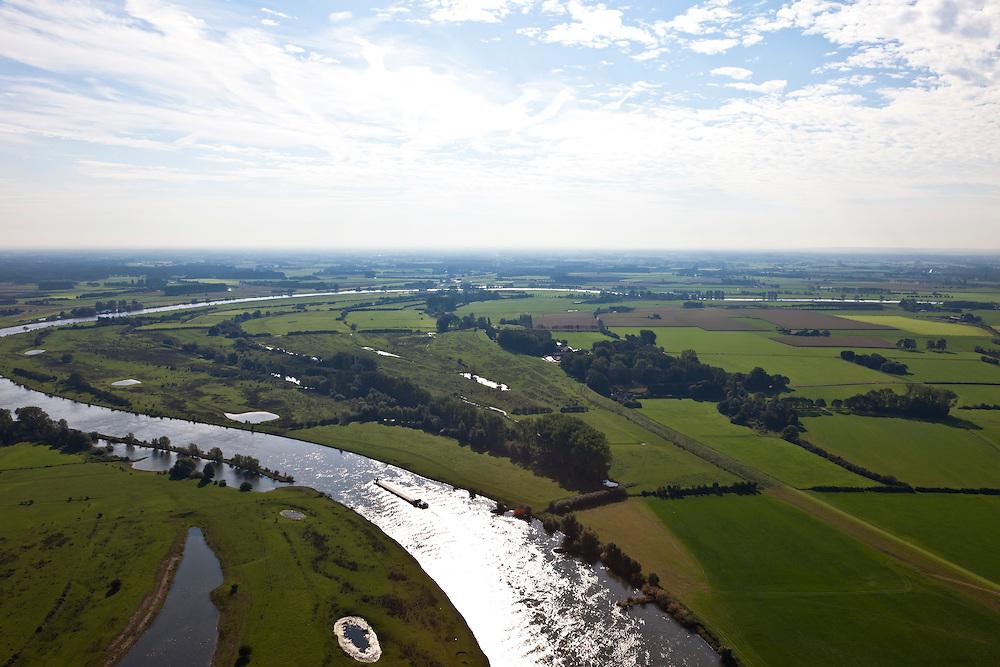 Nederland, Gelderland, Gemeente Brummen, 03-10-2010; Cortenoever met Brummense Bandijk, gezien naar het zuidoosten. Plangebied voor dijkverlegging. Er komt een nieuwe dijk, ongeveer een kilometer landinwaarts, rechts in lijn met de weg.  De oude dijk onder in beeld wordt verlaagd en krijgt een uitstroomopening ongeveer tot aan de bosschages. Het middendeel, op het tweede plan, blijft bestaan, de verlaging voor de instroomopening komt rechts aan de horizon. Links de kronkelwaard Reuverswaard (blijft bestaan). .Shifting the Cortenoever dike. The existing dike will move about one km inland (to the right and in line with the road)). The existing dike (below - to the woods) will be reduced in height to the to create exit opening, but the middle section  will remains. The dike on the very right and to the horizon will be reduced reduced in height for the intake opening..luchtfoto (toeslag), aerial photo (additional fee required).foto/photo Siebe Swart