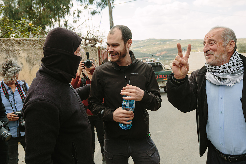 Murad Shteiwi (2nd L), talks with Israeli activist Jonathan Pollak (C), during a weekly demonstration against the expropriation of Palestinian land by Israel and against the closure of the main road leading to Nablus, in the Palestinian village of Kufr Qaddum, West Bank, on February 21, 2020.