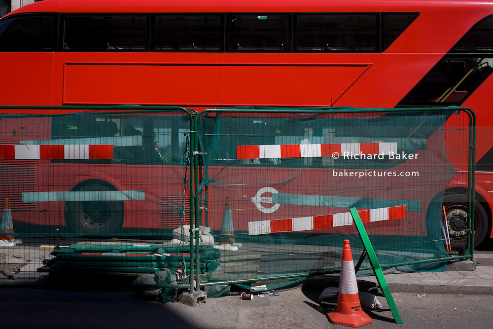London Routemaster bus stopped at lights by construction work in central London.