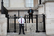 Security guard employees wearing face shields at the National Gallery stand at the bottom of steps leading into a small entrance of the National Gallery during the Coronavirus pandemic, on 29th August 2020, in London, England,