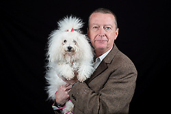© Licensed to London News Pictures. 10/03/2016. Birmingham, UK. Dennis Mulligan with his Bolognese dog Mia at Crufts 2016 held at the NEC in Birmingham, West Midlands, UK. The world's largest dog show, Crufts is this year celebrating it's 125th anniversary. The annual event is organised and hosted by the Kennel Club and has been running since 1891. Photo credit : Ian Hinchliffe/LNP
