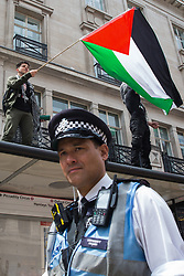 London, UK. 26th June, 2021. A pro-Palestinian activist waves a flag from the top of a bus shelter during the United Against The Tories national demonstration organised by the People's Assembly Against Austerity in protest against the policies of Prime Minister Boris Johnson's Conservative government. The demonstration contained blocs from organisations and groups including Palestine Solidarity Campaign, Stand Up To Racism, Stop The War Coalition, Extinction Rebellion, Kill The Bill and Black Lives Matter as well as from trade unions Unite and the CWU.
