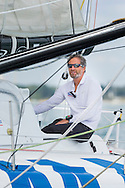 Michel Desjoyaux aboard the french IMOCA 60 yacht SMA at the start of the 90th anniversary Rolex Fastnet Race on the Solent. A record fleet of 370 yachts will compete to win the Fastnet Challenge Cup.<br /> The 600 nautical mile race starts in Cowes, Isle of Wight, heading to the Fastnet Rock off the south west coast of Ireland and finishes in Plymouth.<br /> It is the world's biggest offshore race with 75% amateur sailors and professional yachtsmen competing against each other. <br /> Picture date Sunday 16th August, 2015.<br /> Picture by Christopher Ison. Contact +447544 044177 chris@christopherison.com