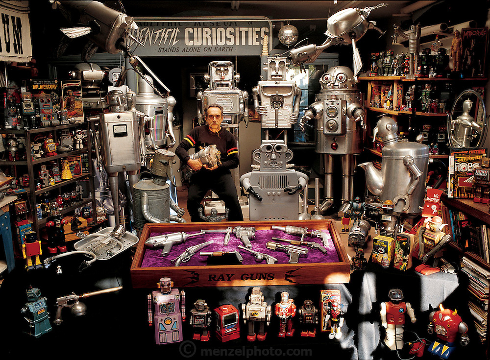 Surrounded by his robot toys and sculptures, Clayton Bailey of Port Costa, California, is living proof that not everyone feels threatened by the prospect of being surrounded by mechanical human beings. In the studio behind his home, Bailey stands among the large robots he has sculpted since retiring as a professor of art from California State University, Hayward. He and his wife, Betty, have collected robot and space toys for the past 30 years. From the book Robo sapiens: Evolution of a New Species, page 230-231.
